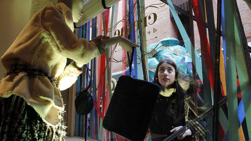 Foto: Una mujer observa una vitrina en una tienda de la marca de moda Desigual. (EFE)
