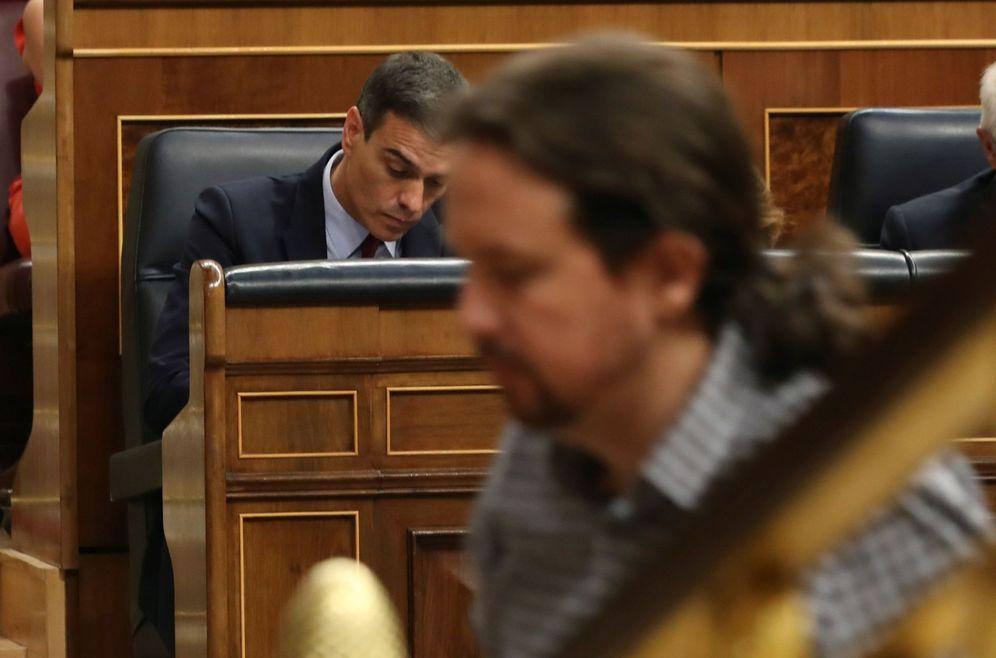 Foto: Pablo Iglesias pasa delante de Pedro Sánchez, este 22 de julio durante el debate de investidura en el Congreso. (EFE)