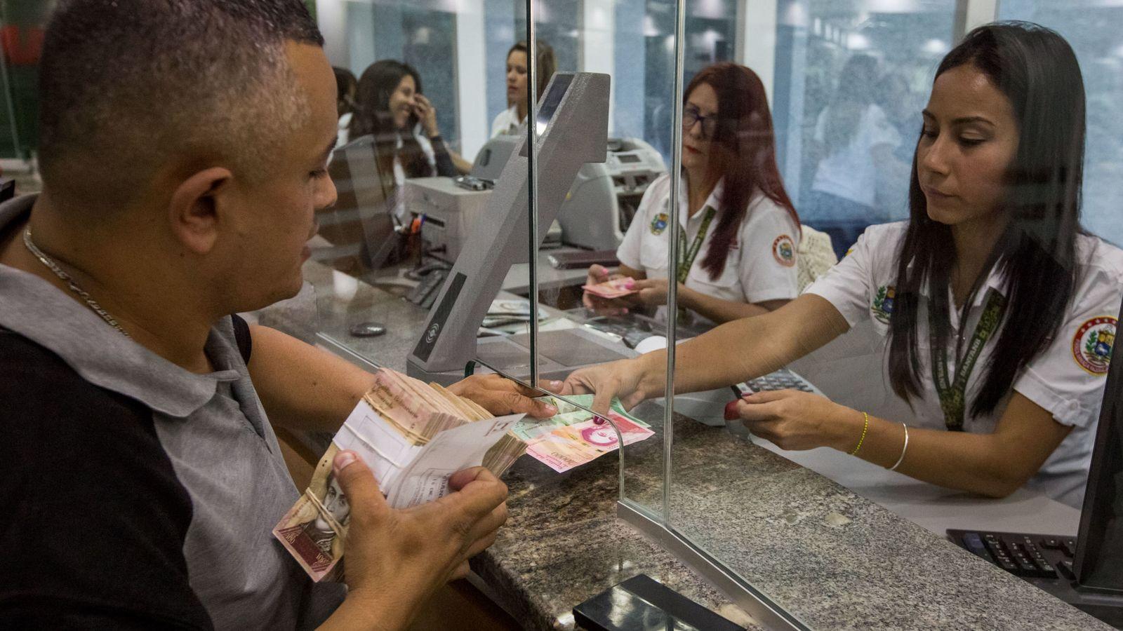 Foto: Emleados de banca empiezan a operar con los nuevos billetes en una entidad de Caracas, el 16 de enero de 2017 (EFE)