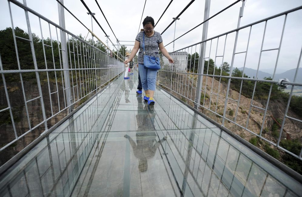 Foto: Turistas observan la altura mientras cruzan una pasarela de cristal en el Parque Nacional Shiniuzhai, en la provincia de Hunan, China (Reuters).