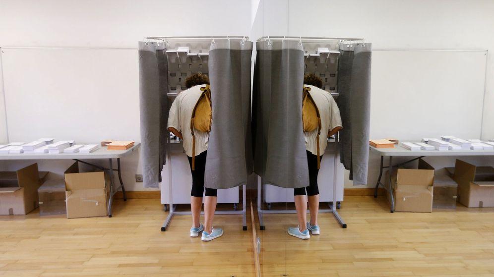 Foto: Un elector, con su imagen reflejada en un espejo, elige su papeleta para ejercer su derecho al voto. (EFE)