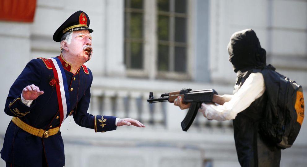 Foto: El artista Francisco Pacheco acribilla a Augusto Pinochet en pleno centro de Santiago de Chile. (EFE)