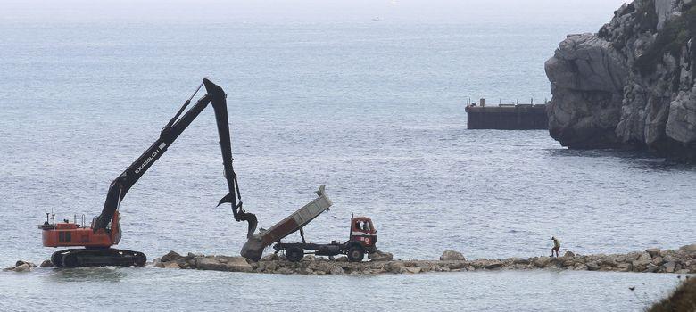 Foto: Una máquina excavadora continúa los trabajos correspondientes al proyecto del arrecife artificial en la parte este del Peñón. (EFE)