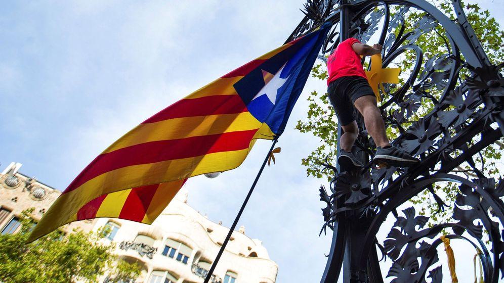 Foto: Un hombre coloca un lazo amarillo durante la manifestación independentista convocada con motivo de la Diada. (EFE)