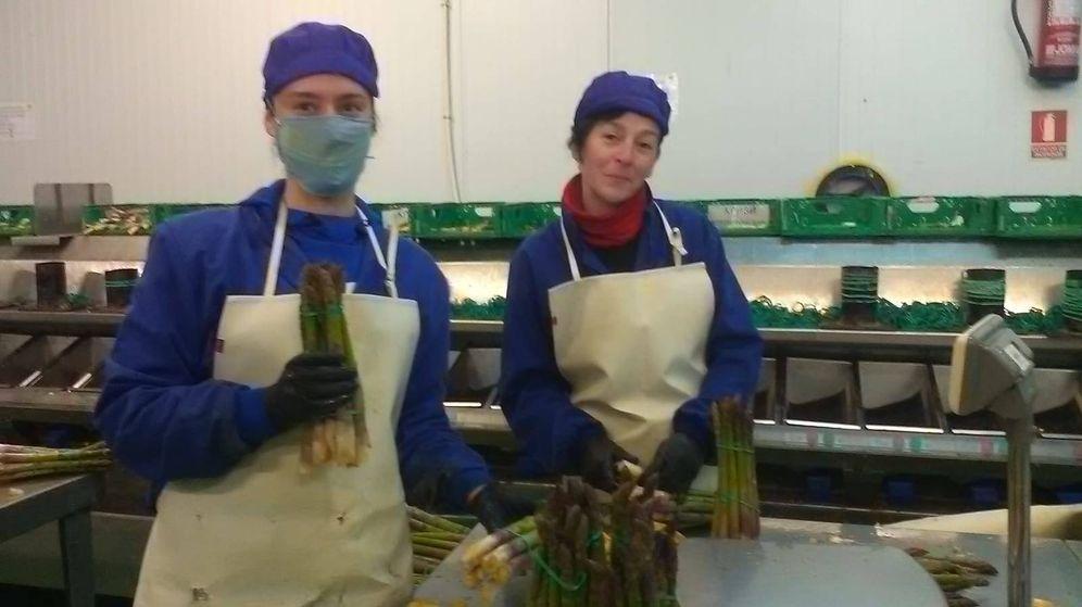 Foto: Esther Rocha, con mascarilla, junto a una compañera que se la retira solo para la foto, en la nave donde trabaja