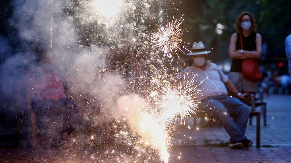 Foto: Dos personas observan arder pirotecnia en el Eixample de Barcelona durante la noche más corta del año (EFE)