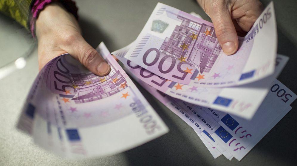 Foto: Un empleado de banca muestra 5.000 euros en billetes de 500. (EFE)
