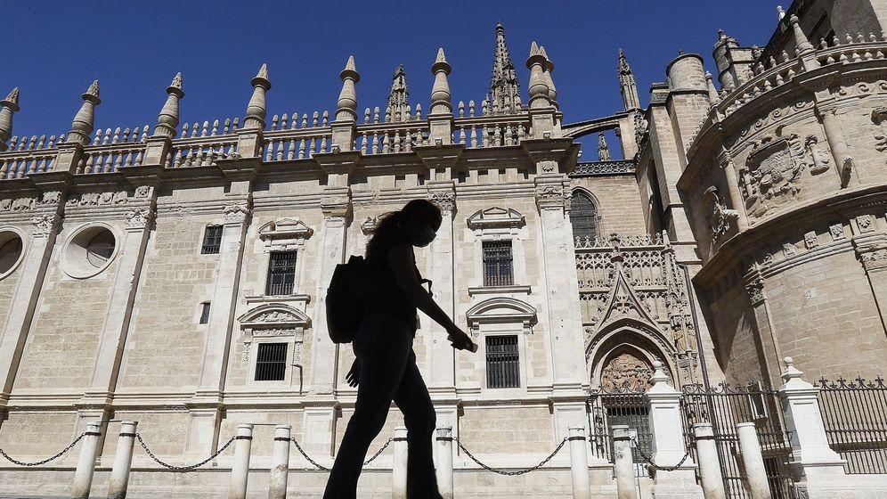 Foto: Una mujer camina delante de la Catedral de Sevilla. (EFE)