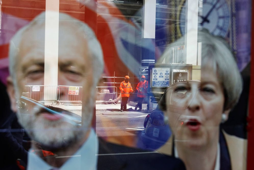 Foto: Trabajadores reflejados en una ventana con las imágenes de Jeremy Corbyn y Theresa May, en Londres. (Reuters)