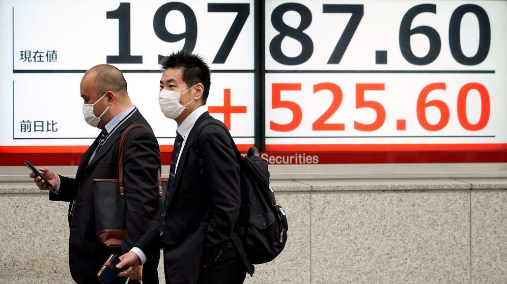 Foto: Dos personas con mascarillas protectoras caminan junto a un cartel que indica los movimientos de la Bolsa de Tokio. (EFE)