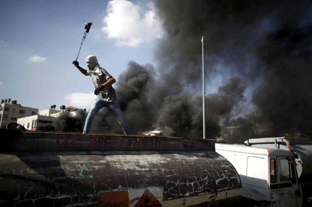 Foto: Un palestino lanza piedras contra soldados israelíes durante enfrentamientos en la colonia judía de Beit El, cerca de Ramala, en Cisjordania (Reuters).