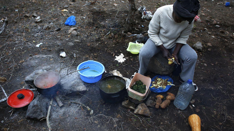 Rachel, una inmigrante de Camerún, cocina en el campamento clandestino de Bolingo, cerca de Melilla (Reuters).