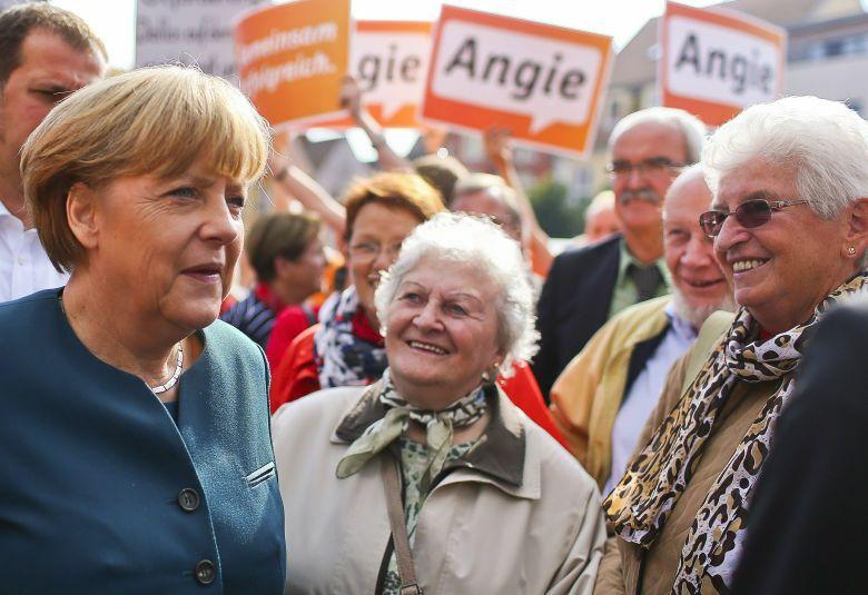 La canciller habla con varios ciudadanos durante un acto de campaña electoral en una plaza de Barth (Efe).