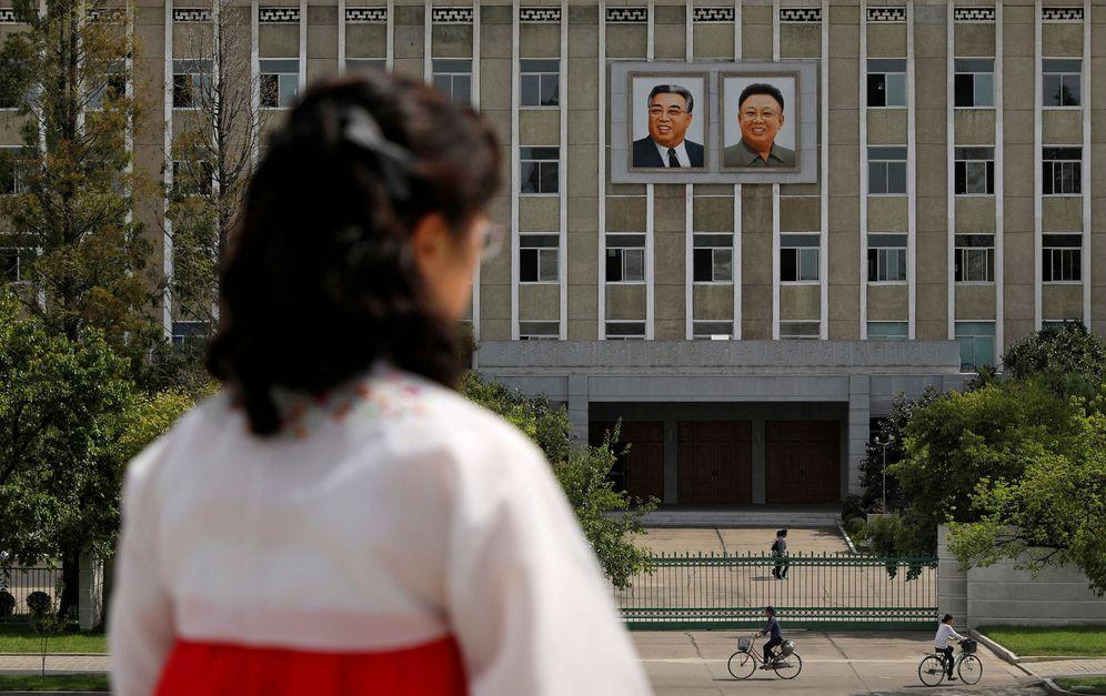 Foto: Una mujer frente a los retratos de los fallecidos líderes norcoreanos Kim Il-sung y Kim Jong-il en una fachada en Pyongyang, en septiembre de 2018. (Reuters)