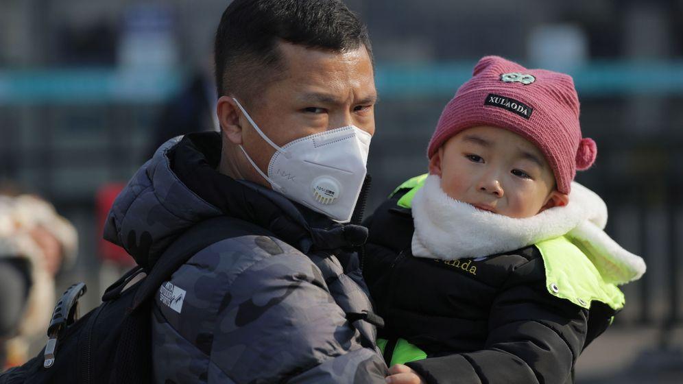 Foto: Un padre con mascarilla y su hijo caminan por Pekín. (Reuters)