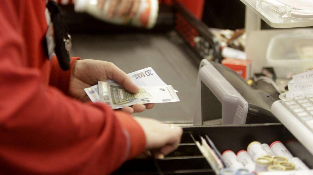 Foto: Una cajera de un supermercado devuelve el cambio a un cliente. (EFE)