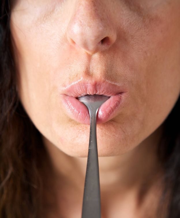 Foto: Una mujer chupa una cuchara. (iStock)