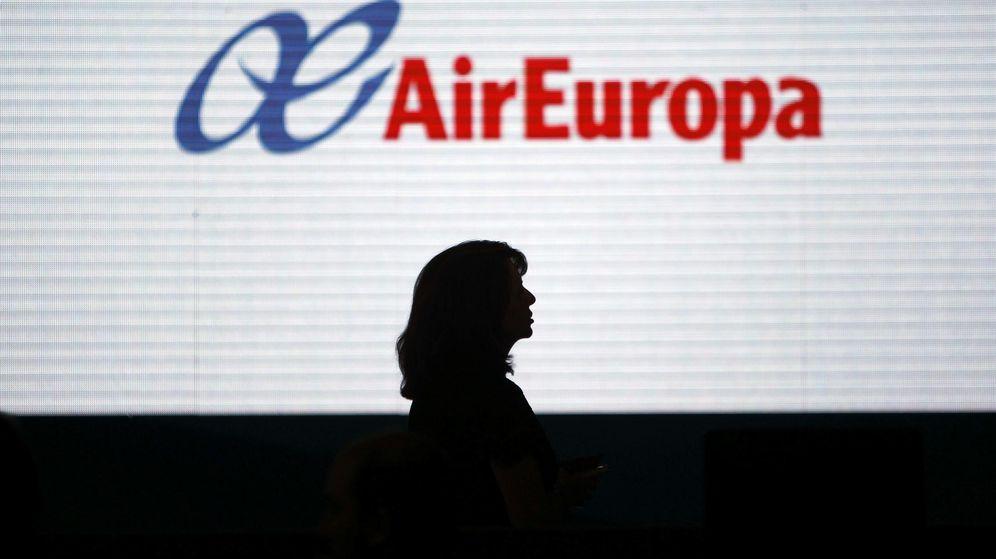 Foto: La silueta de una mujer se dibuja sobre una pantalla con el logotipo de Air Europa. (EFE)