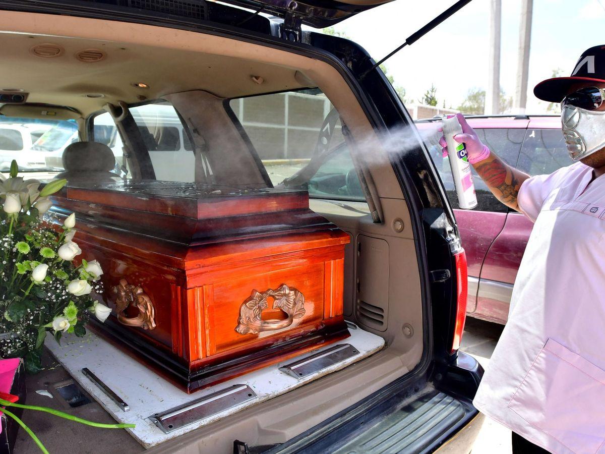 Foto: Un empleado funerario mientras desinfecta un féretro en México. (EFE)