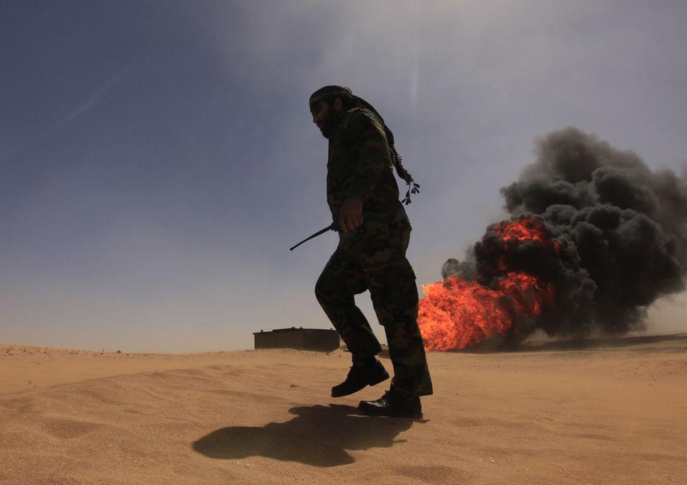 Foto: Un miembro de los cuerpos de seguridad pasa ante un gasoducto en llamas tras una explosión, ubicado a 18 kilómetros de Ajdabiyah, Libia. (Reuters)