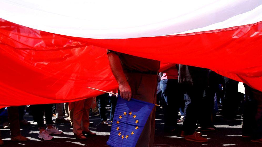 Foto: Un hombre sujeta una bandera de la Unión Europea debajo de una gigantesca bandera polaca. (Reuters)