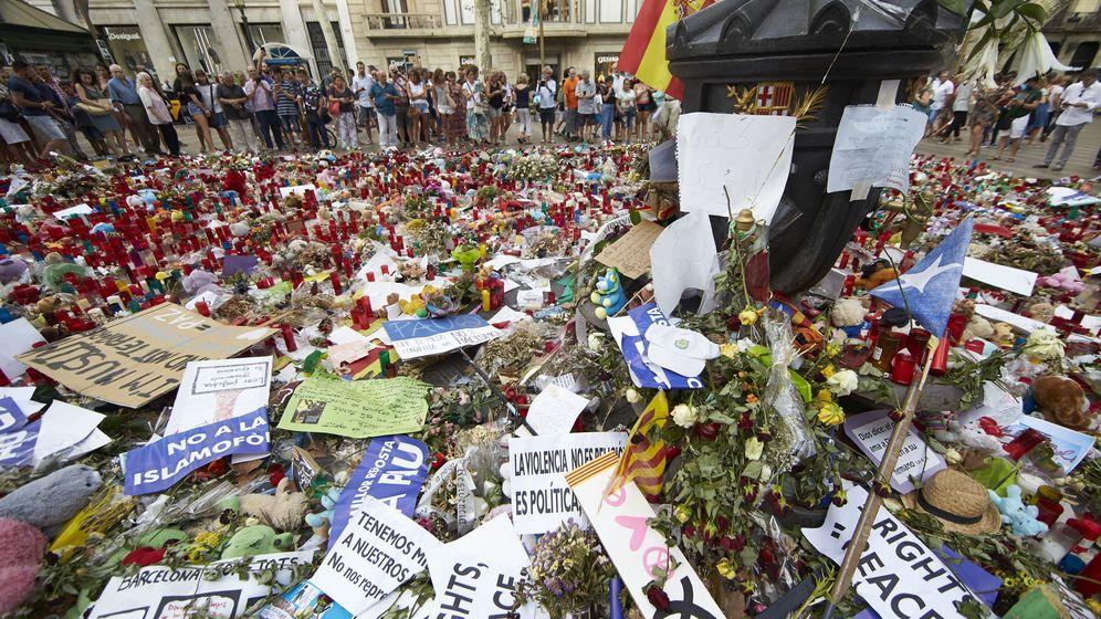 Foto: Ciudadanos y turistas observan los ramos de flores, velas, peluches y dedicatorias a las víctimas del atentado del pasado 17 de agosto. (Efe)