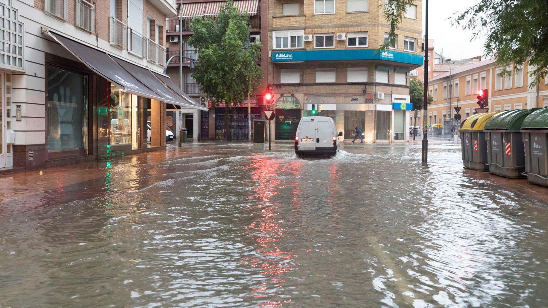 Un coche circula esta mañana por la calle Princesa de Murcia. (EFE)