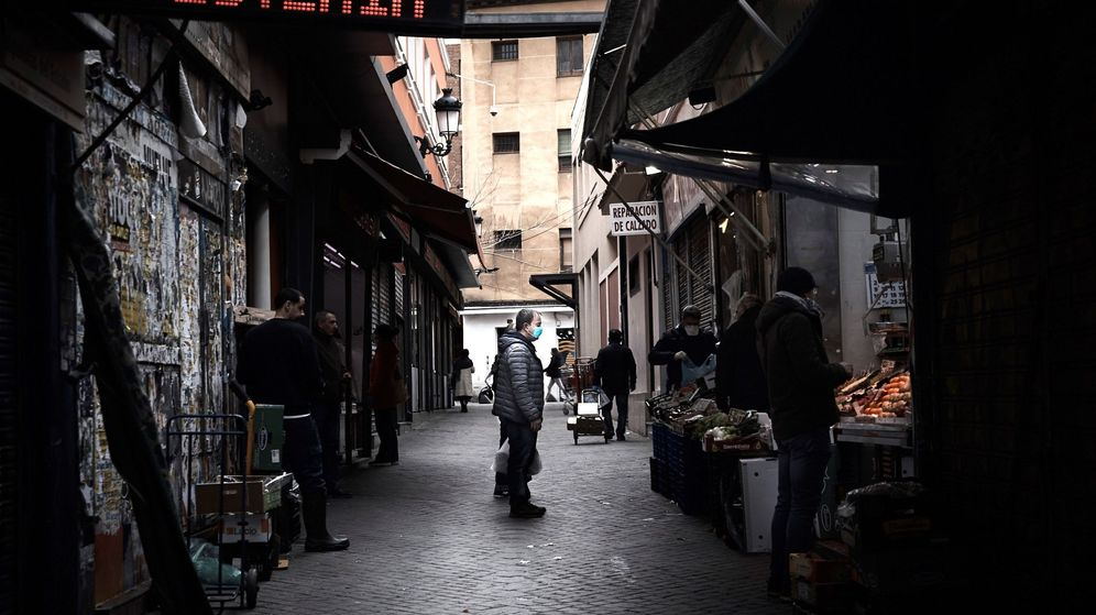Foto: Un hombre espera su turno en una frutería del Mercado de Antón Martín en Madrid. (EFE)