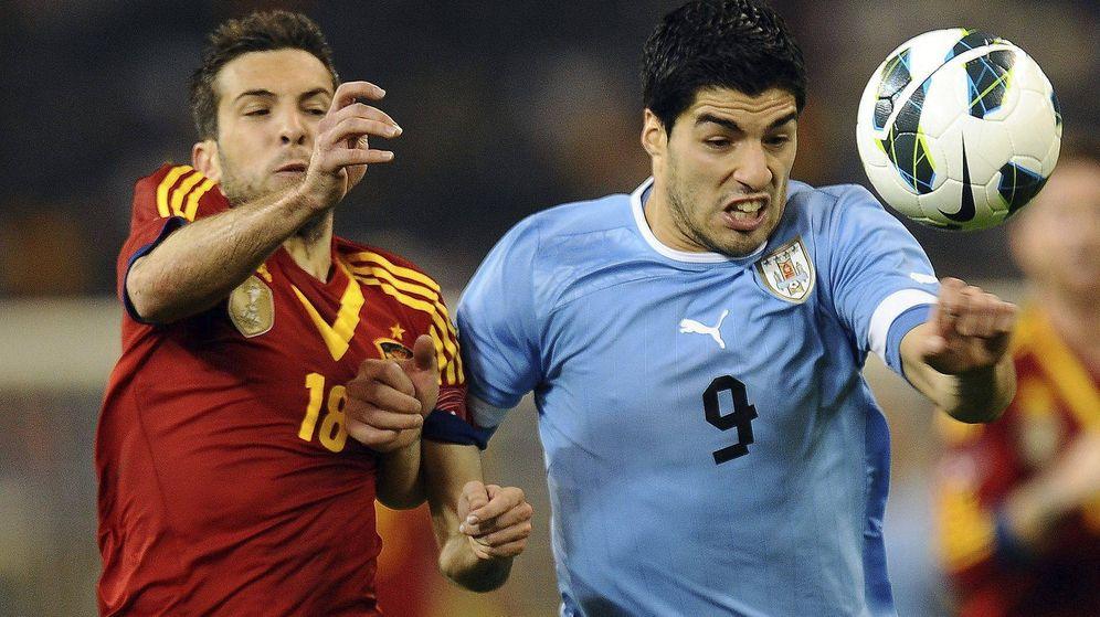 Foto: El español Jordi Alba y el uruguayo Luis Suárez disputan un balón en el amistoso internacional jugado en febrero de 2013 en Qatar. (EFE)