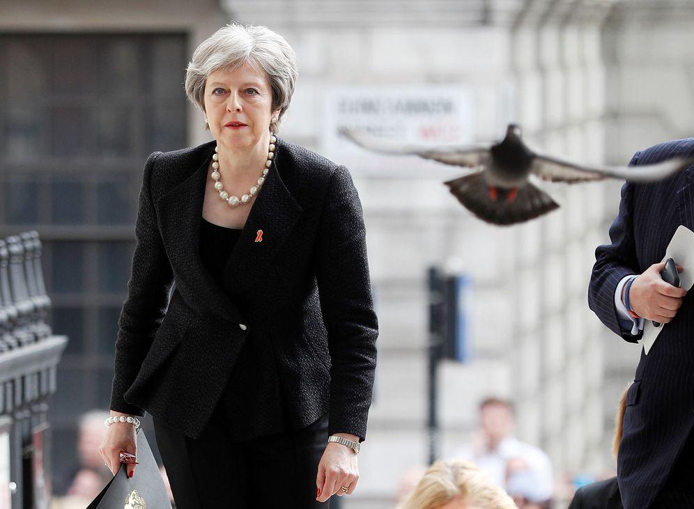Foto: Una paloma alza el vuelo al paso de Theresa May durante un acto en Londres, el 23 de abril de 2018. (Reuters)