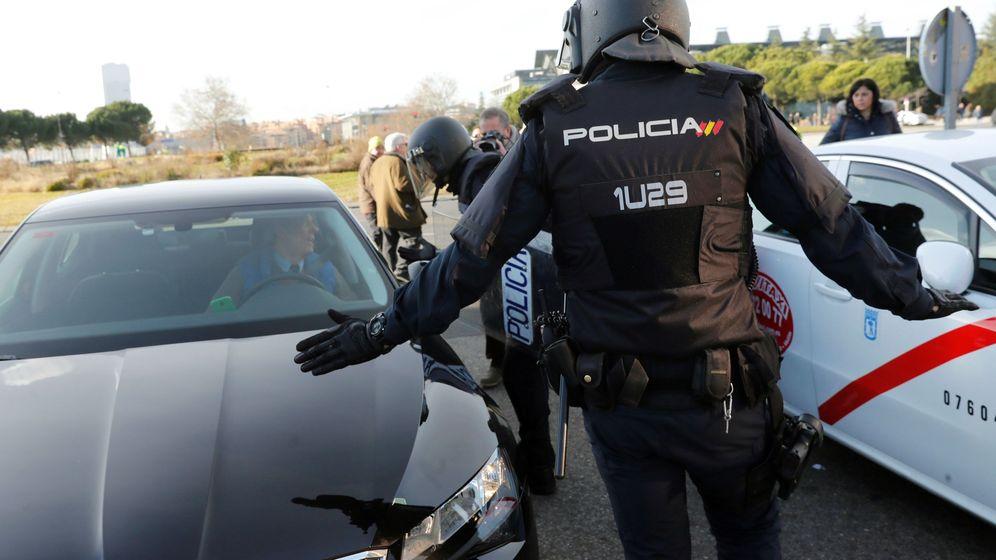 Foto: Efectivos de la Policía Nacional entre un vehículo de licencia VTC y un taxi a las puertas del recinto ferial de IFEMA. (EFE)