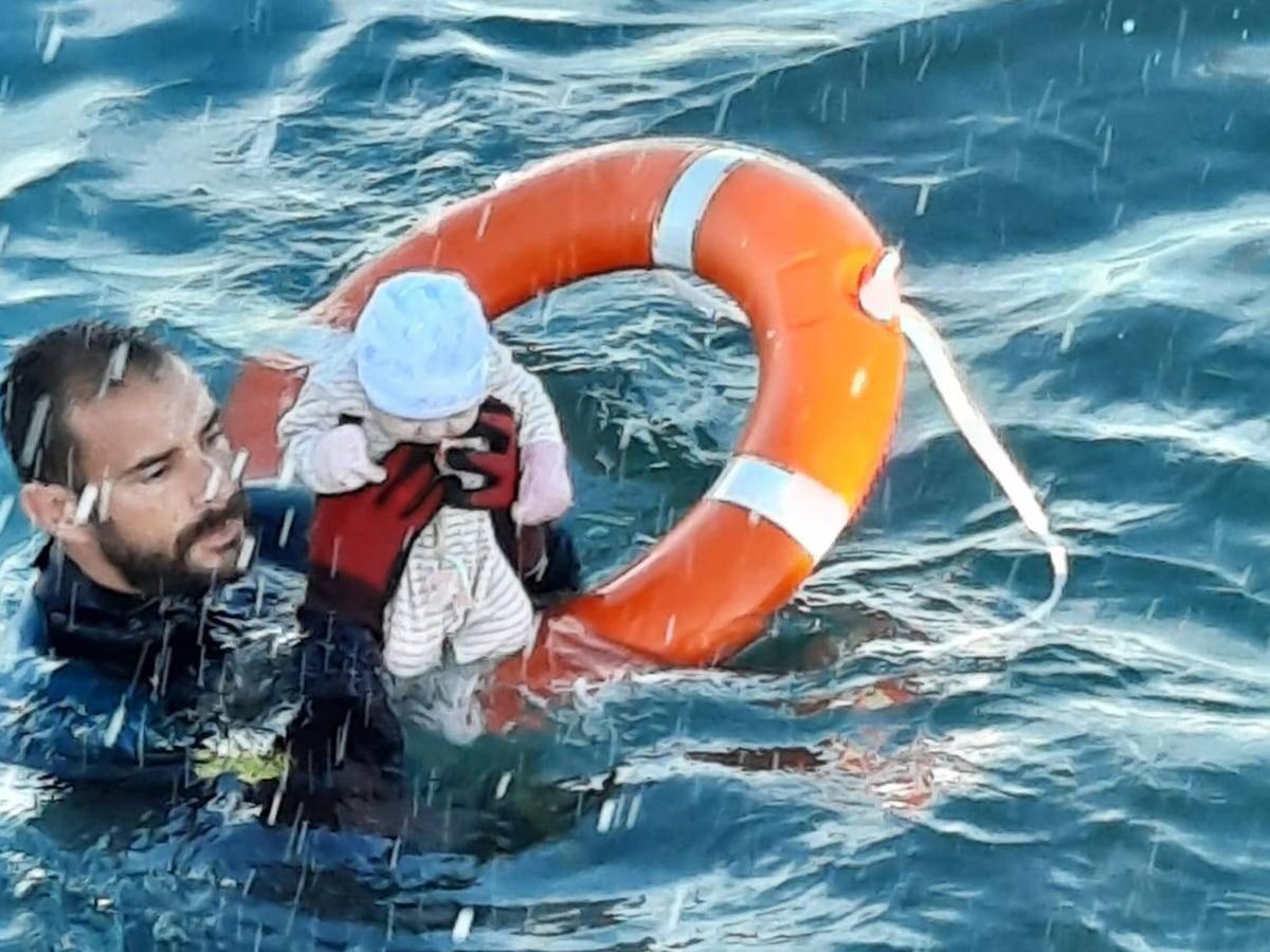 Foto: Un agente de la Guardia Civil rescata a un bebé del agua durante el paso de inmigrantes a nado en Ceuta (Twitter/Guardia Civil)