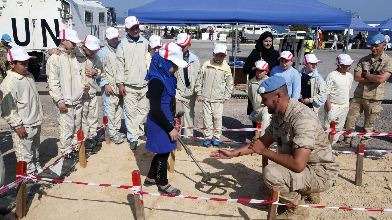 Un soldado de la ONU enseña a nos escolares cómo se usa un detector, en los cuarteles de la UNIFIL en Naqoura, en abril de 2014 (Reuters)