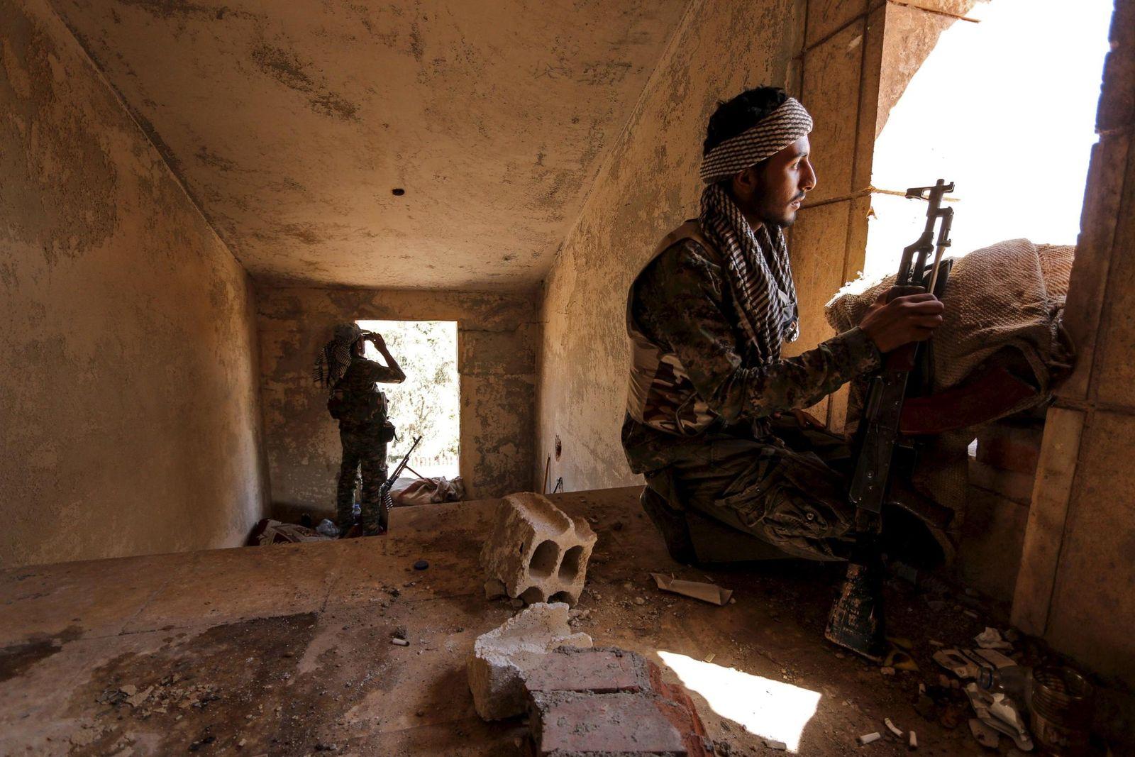 Foto: Un combatiente de las YPG kurdas observa el frente desde el interior de un edificio en la ciudad siria de Hasaka, el 22 de julio de 2015 (Reuters).