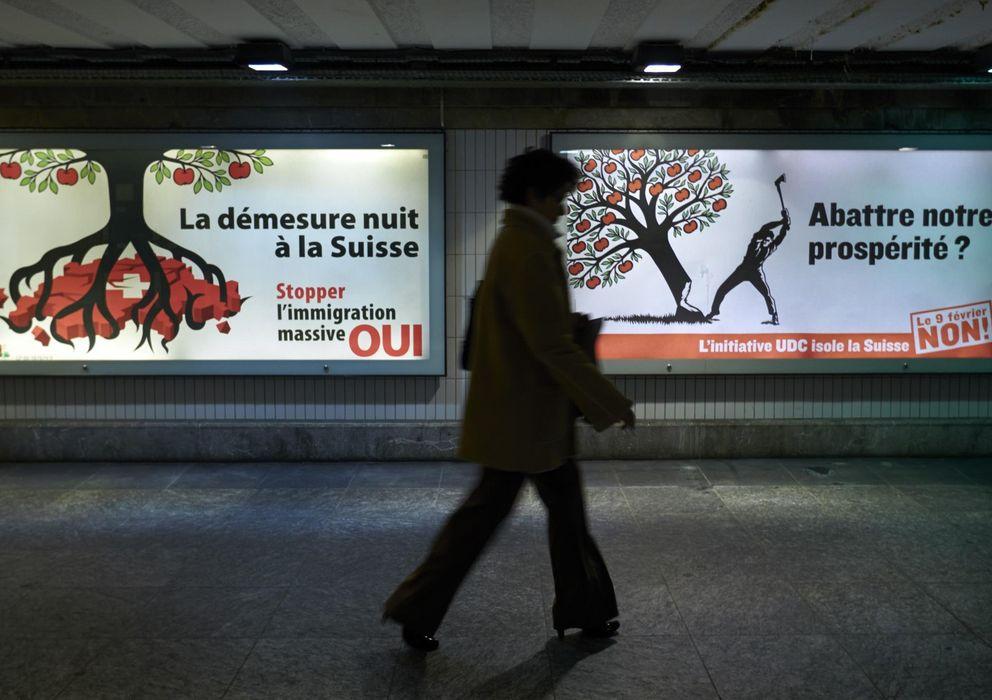 Foto: Una mujer pasa ante dos carteles sobre la inmigración en Lausana. (Reuters)