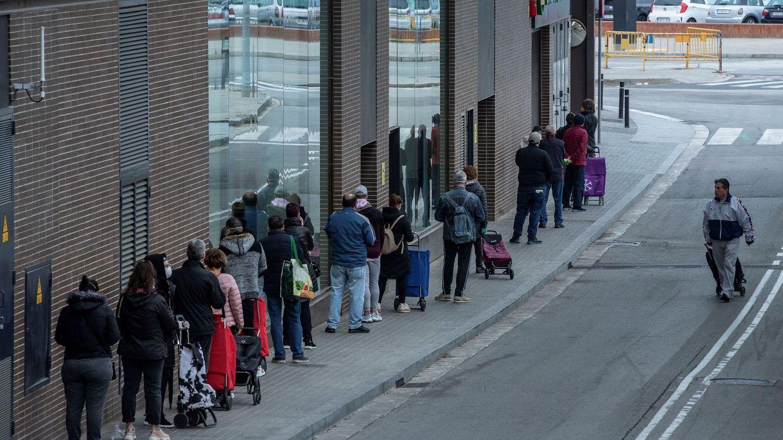 Varias personas esperan para entrar en un supermercado de Nou Barris, Barcelona. (EFE)