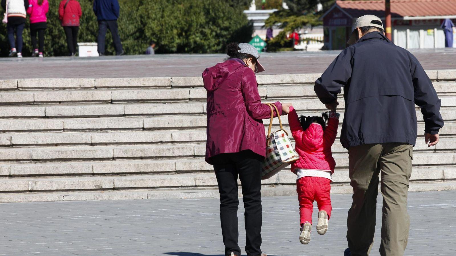 Foto: Dos abuelos sacan de paseo a su nieta en un parque de Pekín (China). (EFE)