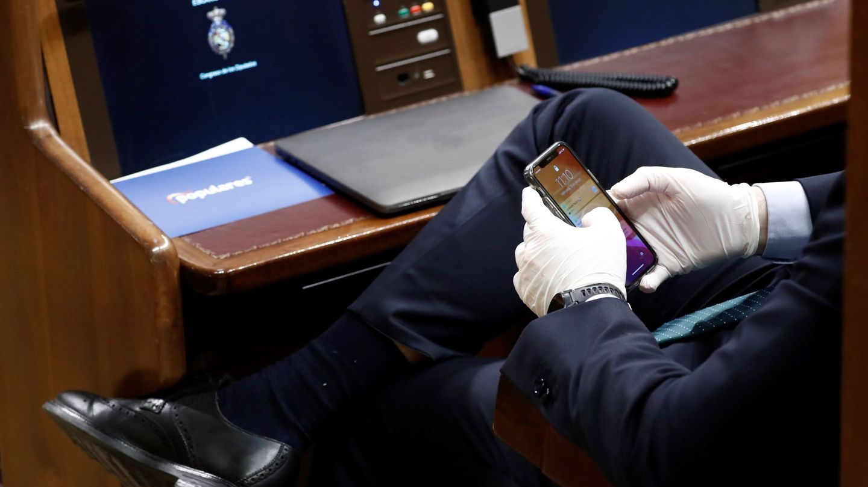 Un diputado consulta su móvil con unos guantes durante el pleno extraordinario de la semana pasada. (EFE)