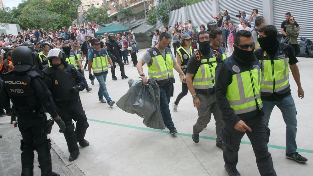 Foto: Agentes de la Policía Nacional y la Guardia Civil retiran urnas del IES Tarragona. (EFE)