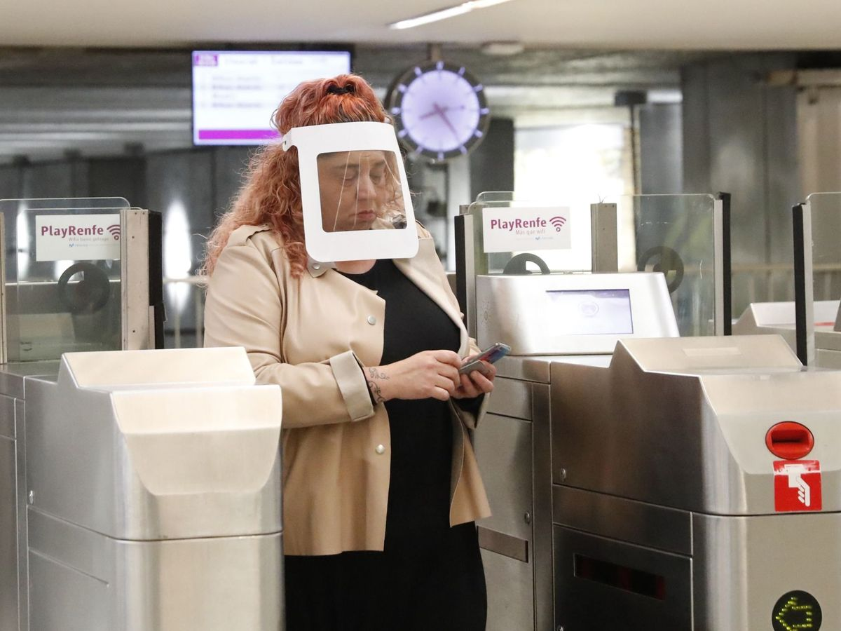 Foto: Una mujer protegida con una pantalla individual sale de la estación de Cercanías de Renfe en Bilbao. (EFE)