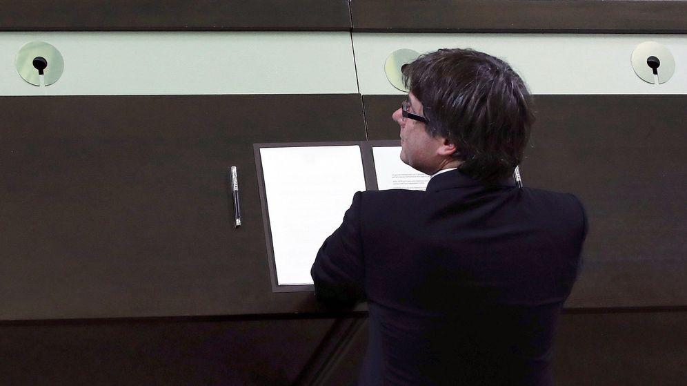 Foto: El presidente de la Generalitat, Carles Puigdemont, firma el documento sobre la independencia. (EFE)