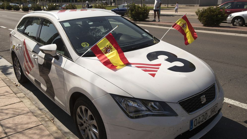 Foto: Un coche de TV3, con la luna rota y en el que los manifestantes han colocado dos banderas de España. (EFE)