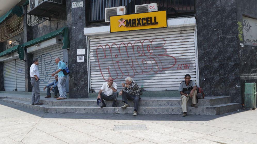 Foto: Varias personas conversan a las afueras de locales comerciales cerrados debido a un apagón en Caracas (Venezuela). (EFE)