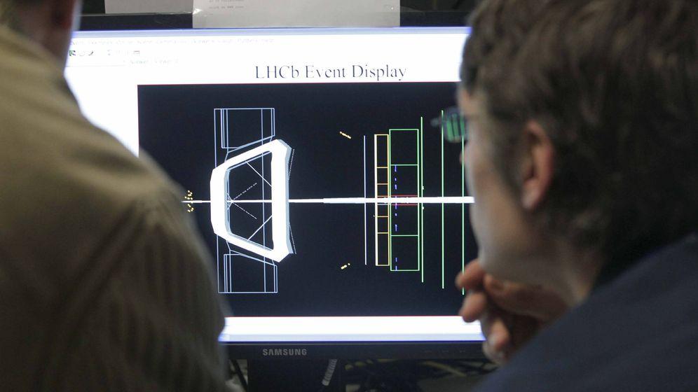 Foto: Un par de científicos observan una de las pantallas en la sala de control de experiencias del LHCb (EFE)