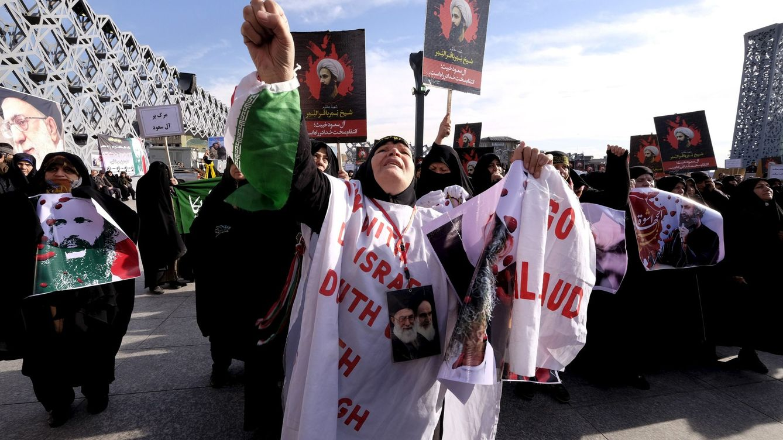 Foto: Una mujer iraní con fotografías del clérigo Nimr Baqir al Nimr durante una protesta en Teherán tras su ejecución, el 4 de enero de 2016. (Reuters).