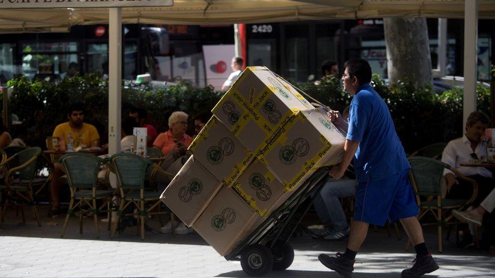 Foto: Un hombre transporta cajas en el centro de Barcelona. (EFE)