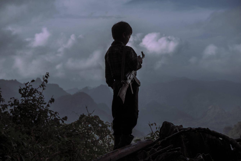 Foto: Chi Vang, de 10 años, contempla las montañas de Laos con un AK-47, en una imagen del documental El Ejército Perdido de la CIA (Foto: Sergio Caro).