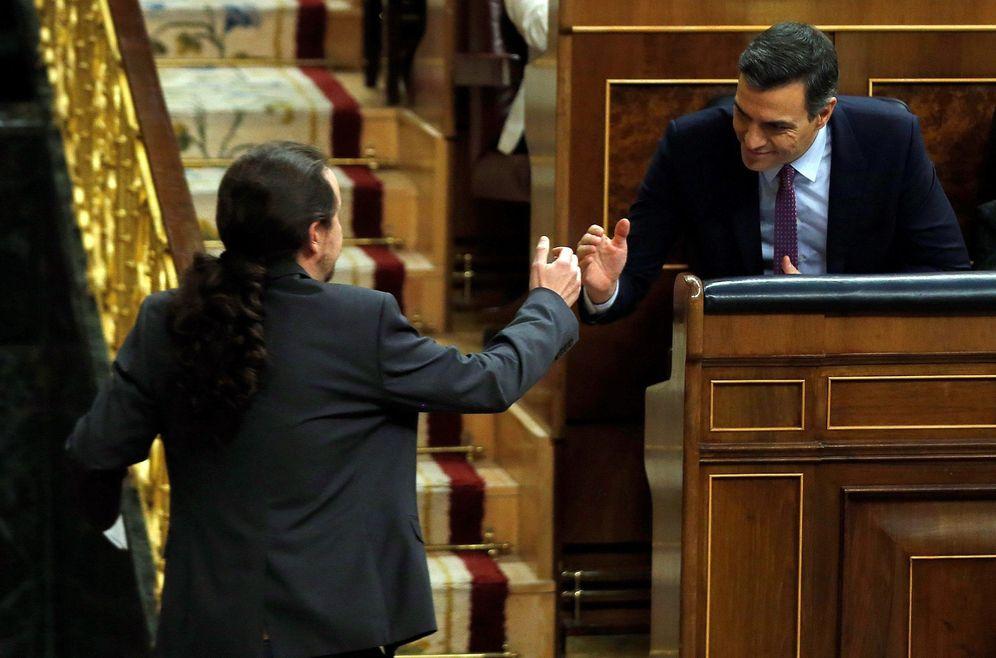 Foto: Pedro Sánchez y Pablo Iglesias estrechan sus manos tras la intervención del líder de Unidas Podemos en el debate de investidura en el Congreso, este 4 de enero. (EFE)
