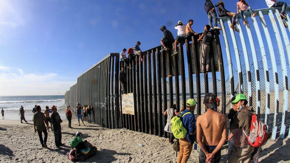 Foto: Migrantes escalan el muro fronterizo hoy en Tijuana, en el estado de Baja California (México). (EFE)