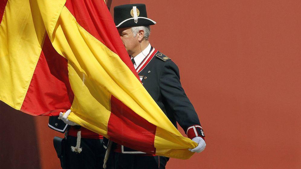 Foto: Un miembro del cuerpo de policía autonómica iza la bandera catalana. (EFE)